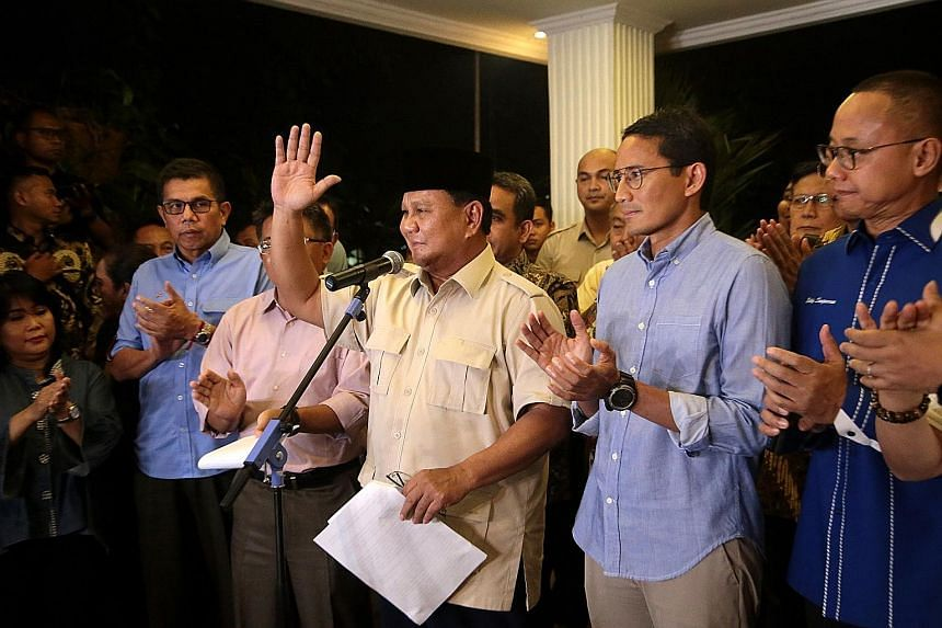Indonesian presidential candidate Prabowo Subianto (centre) with his running mate Sandiaga Uno (right) at a news conference last night following the Constitutional Court's ruling, which Mr Prabowo said he accepted. Prabowo supporters shouting slogans