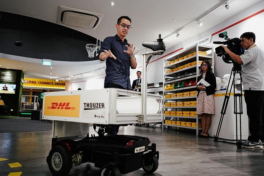 Marketing executive Kenneth Kok showing the use of a robotic trolley that can follow staff around yesterday at DHL Asia Pacific Innovation Centre, where the Connected Logistics Innovation Platform was launched.