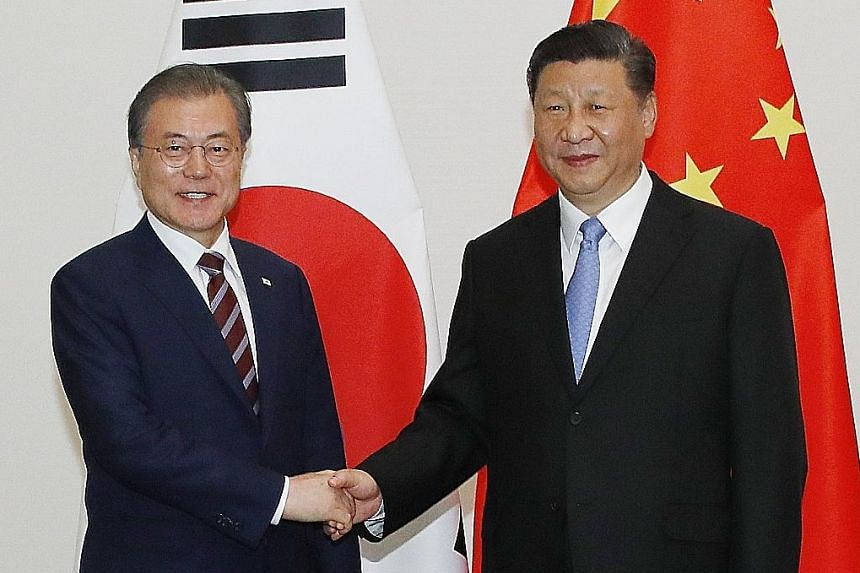 South Korean President Moon Jae-in (left) and Chinese President Xi Jinping meeting before their talks in Osaka yesterday.