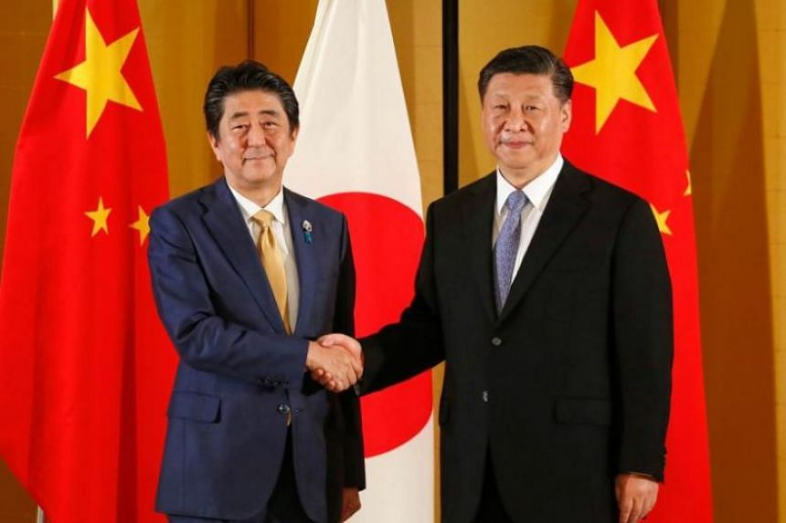 Japanese Prime Minister Shinzo Abe (left) shakes hands with Chinese President Xi Jinping at the start of their talks in Osaka, on June 27, 2019.