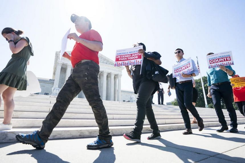 Activists gather outside the US Supreme Court to await the justices' ruling on the Trump administration's attempt to add a citizenship question to the US census in Washington, DC, on June 27, 2019.