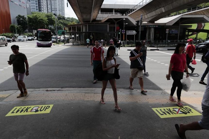 The signs are strategically pasted on the pedestrian ramps on the corners of the intersection and at the entrance to the Ang Mo Kio MRT station.