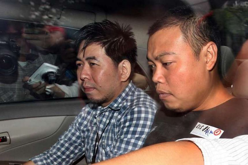 Ex-policeman Iskandar Rahmat, who stabbed to death a 67-year-old businessman in his home in 2013 as well as his 42-year-old son, being escorted in a car by police officers on July 15, 2013.