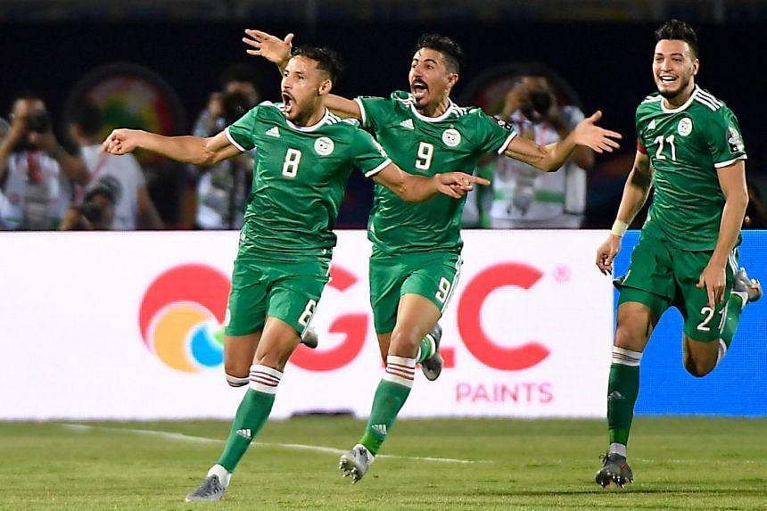 Algeria's forward Youcef Belaili (L) celebrates after scoring.