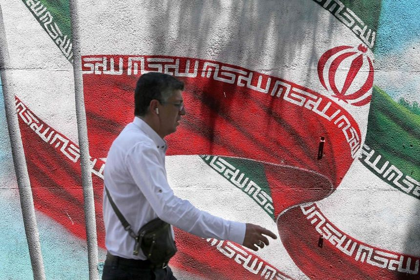 An Iranian man walks past a mural painted with the Iranian flag in Teheran.