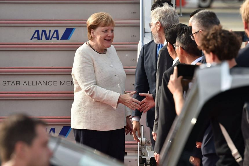Germany's Chancellor Angela Merkel greeted by well-wishers upon her arrival at at Kansai airport in Osaka on June 28, to attend the G-20 Osaka Summit.