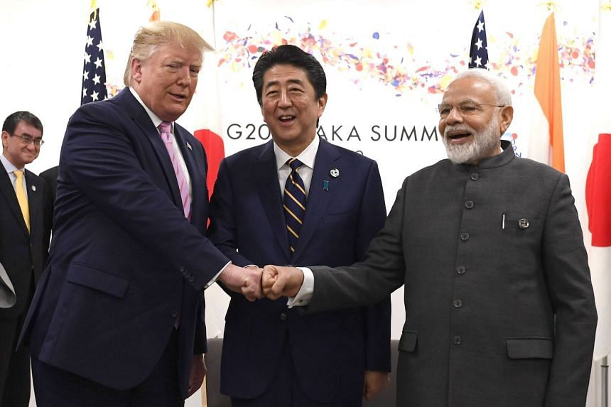(From left) US President Donald Trump, Japan's Prime Minister Shinzo Abe and India's Prime Minister Narendra Modi fist bump during a trilateral meeting on the first day of the G-20 summit.