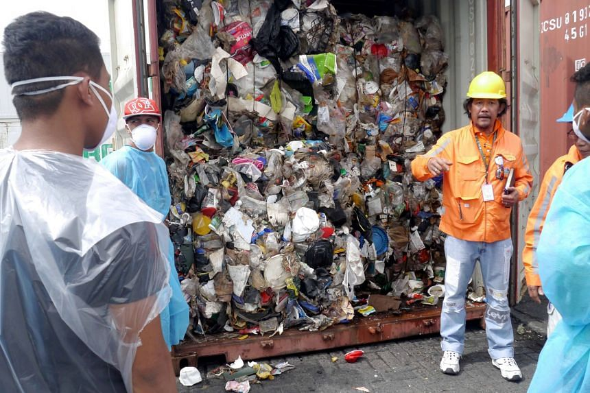 Philippine customs officials inspect cargo containers containing tonnes of garbage shipped by Canada in 2014.