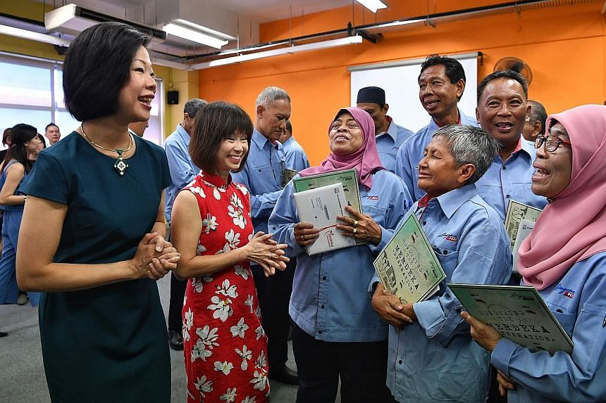 Senior Minister of State for Communications and Information Sim Ann (left) and Senior Minister of State for Health Amy Khor chatting with postal workers from the Merdeka Generation at the SingPost Kallang Delivery Base yesterday after they received t