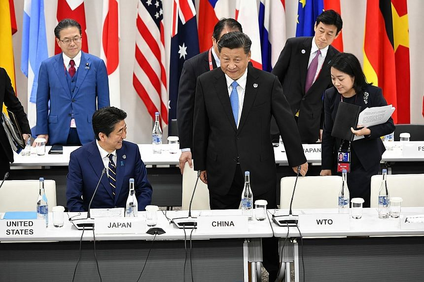 Prime Minister Lee Hsien Loong (front row, fourth from right) and Deputy Prime Minister Heng Swee Keat (behind PM Lee) at a meeting during the G-20 Summit in Osaka yesterday. An agreement to establish the Asian Development Bank's (ADB) new office in