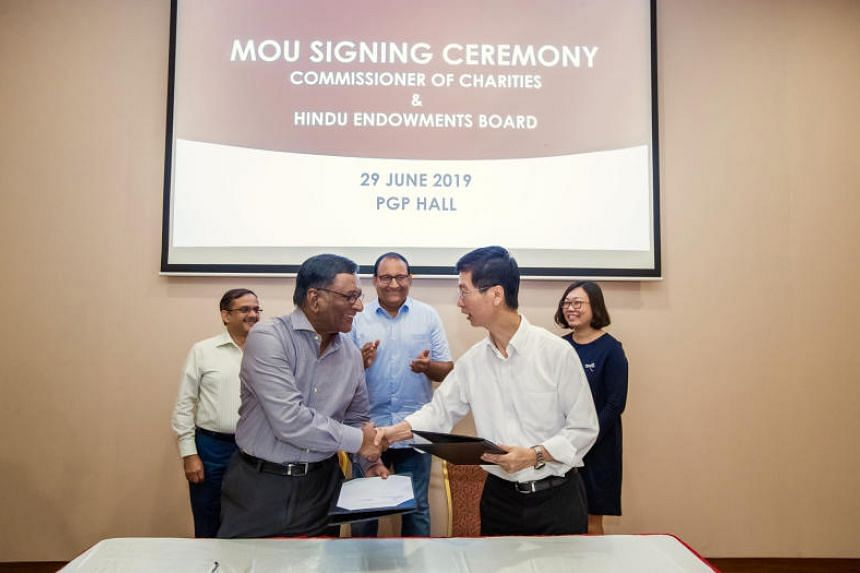 Minister for Communications and Information S. Iswaran witnessing the signing of a memorandum of understanding between Hindu Endowments Board chairman Rangareddy Jayachandran and Commissioner of Charities Ang Hak Seng.