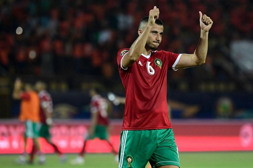 Morocco's defender Romain Saiss celebrates with the fans after the match.