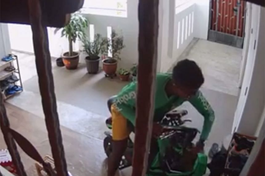 A video posted on social media showed the deliveryman taking a pair of shoes and putting it in his GrabFood delivery bag before riding away from the scene on his personal mobility device.