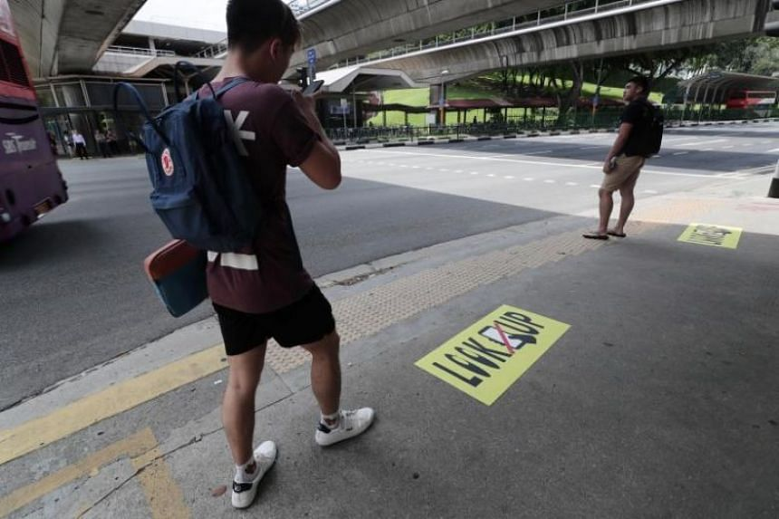 """Large yellow stickers that say """"LOOK UP"""", along with a picture of a mobile phone crossed out, have appeared on the pedestrian ramps on the corners of the intersection and at the entrance to the Ang Mo Kio MRT station."""