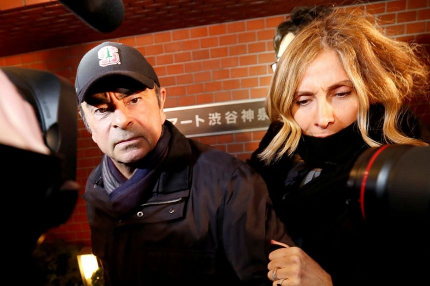 Former Nissan Motor chairman Carlos Ghosn, accompanied by his wife Carole, arriving at his place of residence in Tokyo on March 8, 2019.