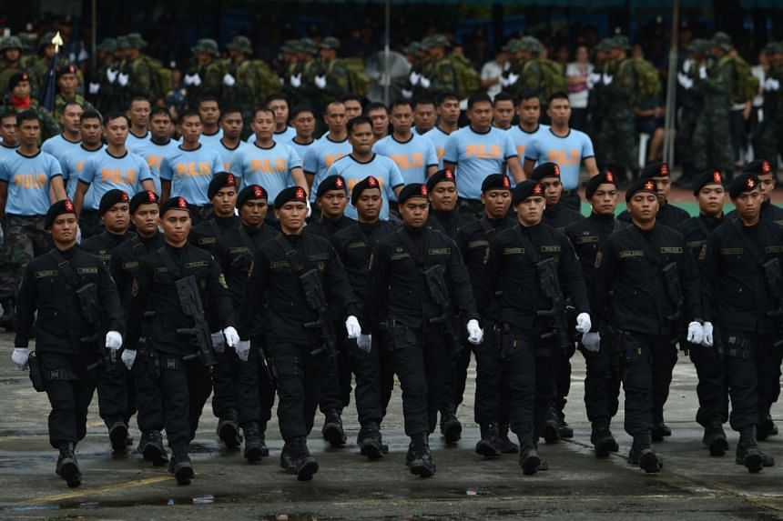 Policemen march in a review of troops during an event at the police national headquarters in Manila on Aug 8, 2018.