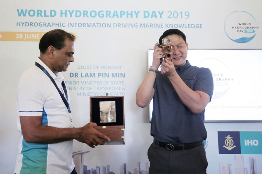 Senior Minister of State for Transport and Health Lam Pin Min trying out a sextant yesterday. With him is Maritime and Port Authority of Singapore assistant chief executive for operations, Captain M. Segar. ST PHOTO: JASON QUAH