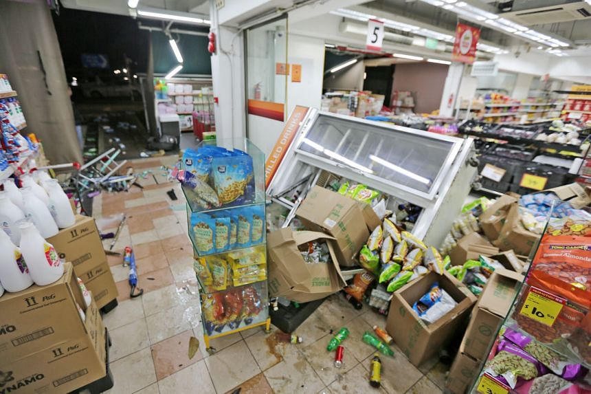 Above: The scene at the Ang Mo Kio supermarket yesterday, after a man drove his car into shelves and items placed outside. There were no reported injuries. Left: The front bumper of the car was damaged.