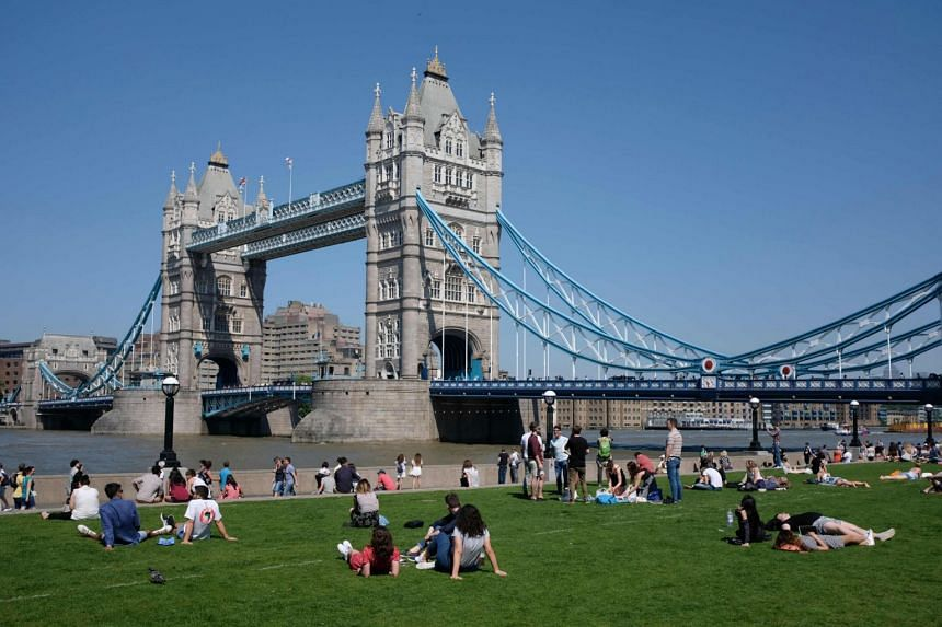 People relax in the hot and sunny weather on the grass beside Tower Bridge and the river Thames in London on May 26, 2017.