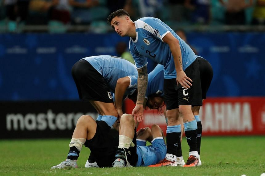 Uruguayan players console Luis Suarez after he missed during the penalty shoot-out.