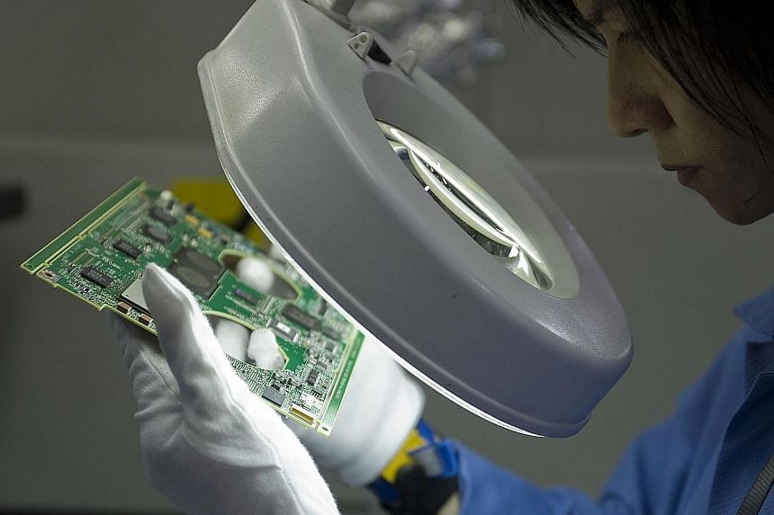 An assembly-line worker in a Venture Corp factory in Singapore. Firms such as Venture Corp that are in the supply chain for well-known global companies are worth tracking in the technology manufacturing sector.
