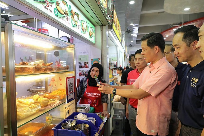 Minister for Trade and Industry Chan Chun Sing scanning the QR code at 49-year-old Madam Siti Naquiah's (left) nasi lemak stall in Ang Mo Kio yesterday, with Senior Minister of State for Trade and Industry Koh Poh Koon (right) looking on.