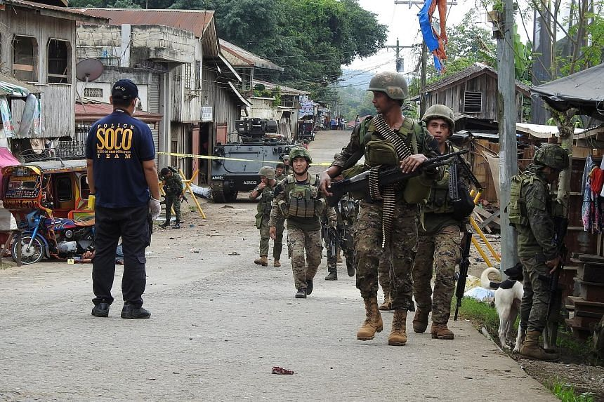Security forces on guard at the site of Friday's attack, which killed eight people, on Jolo island in the Philippines' Sulu province. The prime suspect is the Abu Sayyaf militant group, factions of which have sworn allegiance to the Islamic State in
