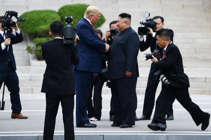 US President Donald Trump and North Korean leader Kim Jong Un shake hands north of the Military Demarcation Line that divides North and South Korea, in the Joint Security Area of Panmunjom in the Demilitarised Zone on June 30, 2019.