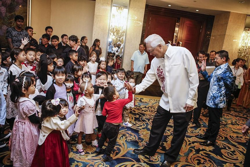 Emeritus Senior Minister Goh Chok Tong giving children high-fives at the charity gala lunch for Arc Children's Centre on June 30, 2019.