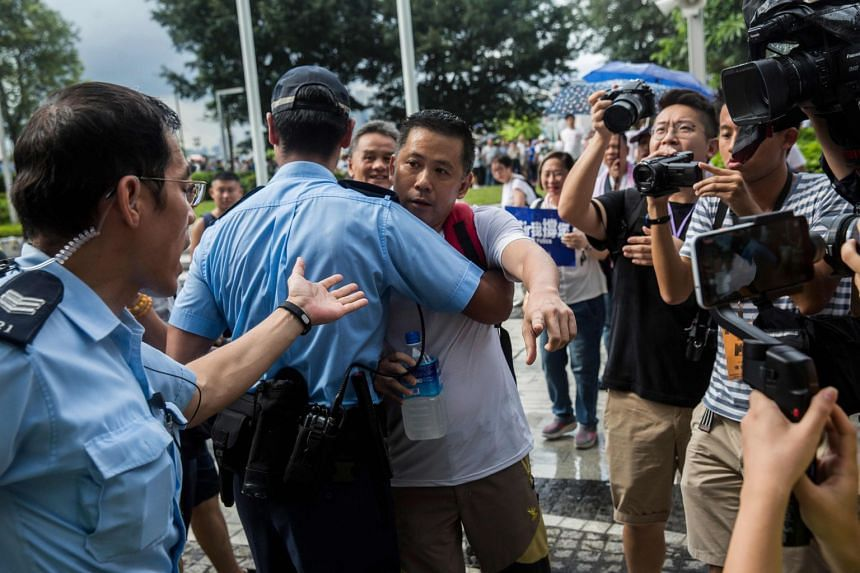 A Hong Kong police officer holding back a pro-police protester as he yells insults at anti-extradition protesters, outside the Legislative Council in Hong Kong on June 30, 2019.