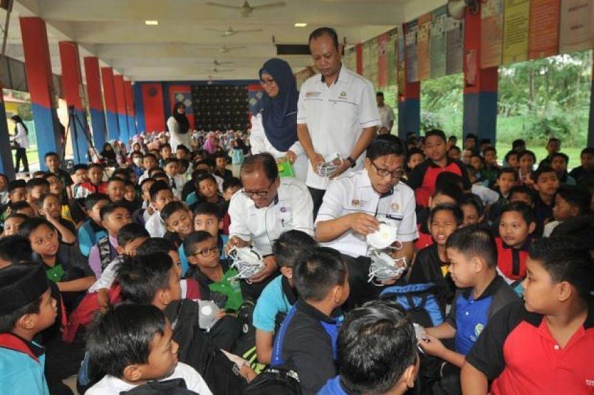 Johor education director Azman Adnan (squatting, front right) distributing masks to students in SK Pasir Gudang 4 on June 30, 2019.