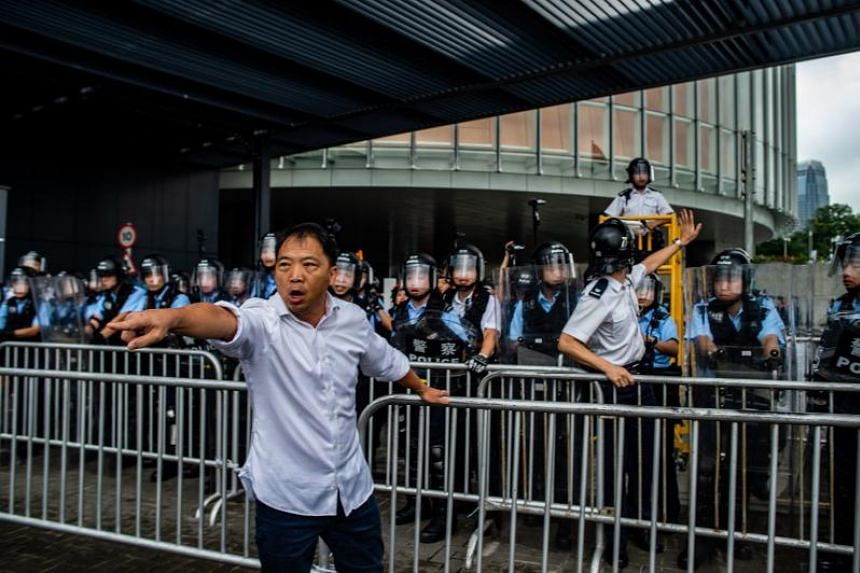 Pro-democracy lawmaker Wu Chi-wai stands before police officers as protesters occupy outside the Legislative Council in Hong Kong on June 12, 2019.