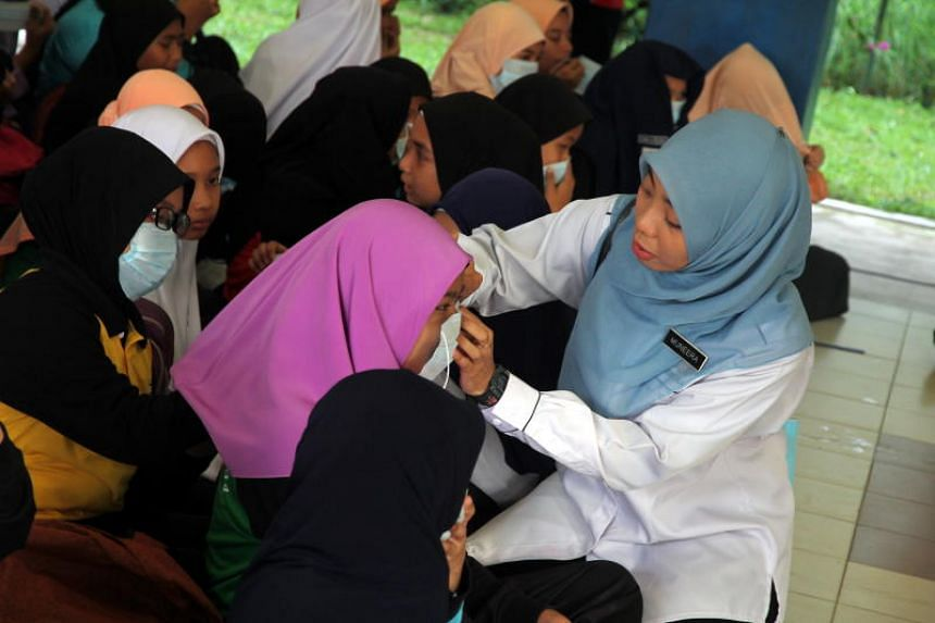 Ms Muneera (right), a teacher at SK Pasir Gudang 4, helping pupils wear their mouth and nose masks during the school session on June 30, 2019.