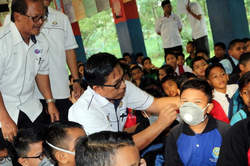 Johor State education department director Azman Adnan helping a pupil wear the mouth and nose mask on June 30, 2019.