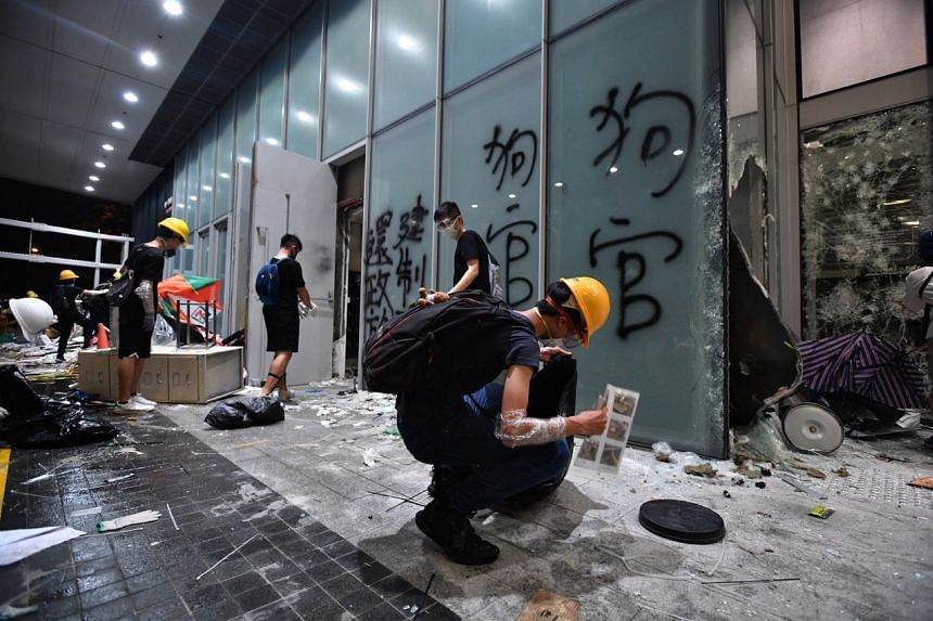 Protesters cleaning up at the entrance of the Legislative Council Complex on July 1, 2019.