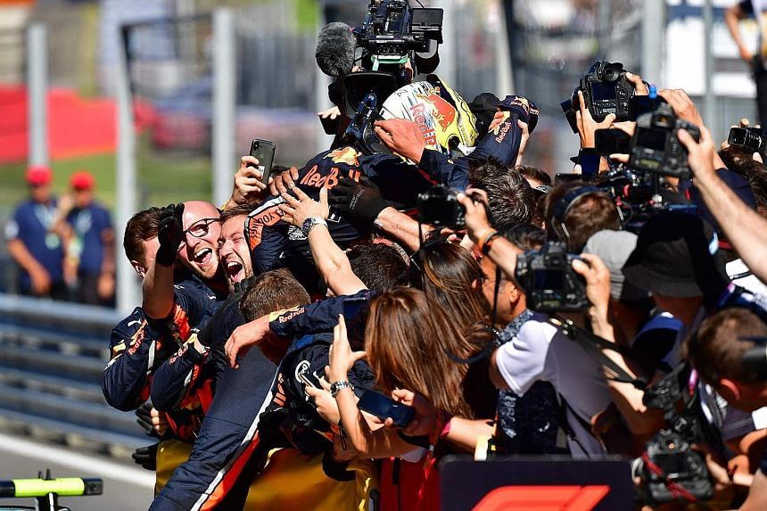 Max Verstappen celebrates with his team of Red Bull engineers after the Austrian Grand Prix in Spielberg yesterday. The Dutchman took the chequered flag for the first time this season after overtaking Charles Leclerc's Ferrari in the closing laps wit