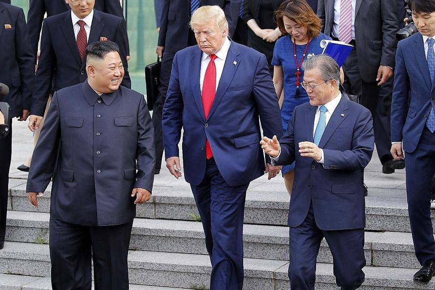 US President Donald Trump heading towards the northern side of the truce village of Panmunjom in the Demilitarised Zone yesterday with North Korean leader Kim Jong Un and South Korean President Moon Jae-in. PHOTO: DPA