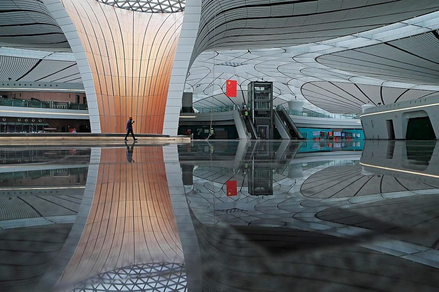 A worker walks inside the terminal hall of the Beijing Daxing International Airport while it was under construction on June 19, 2019.