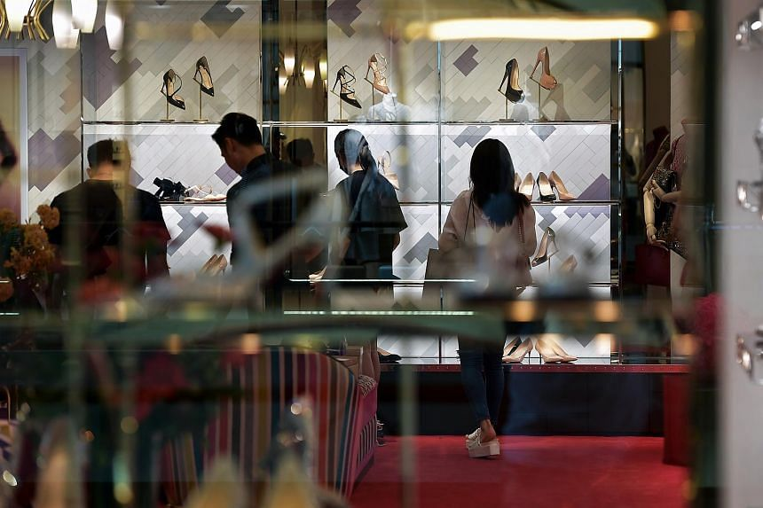 Shoppers at looking at shoes are a store in The Shoppes at Marina Bay Sands, on Feb 14 2018.