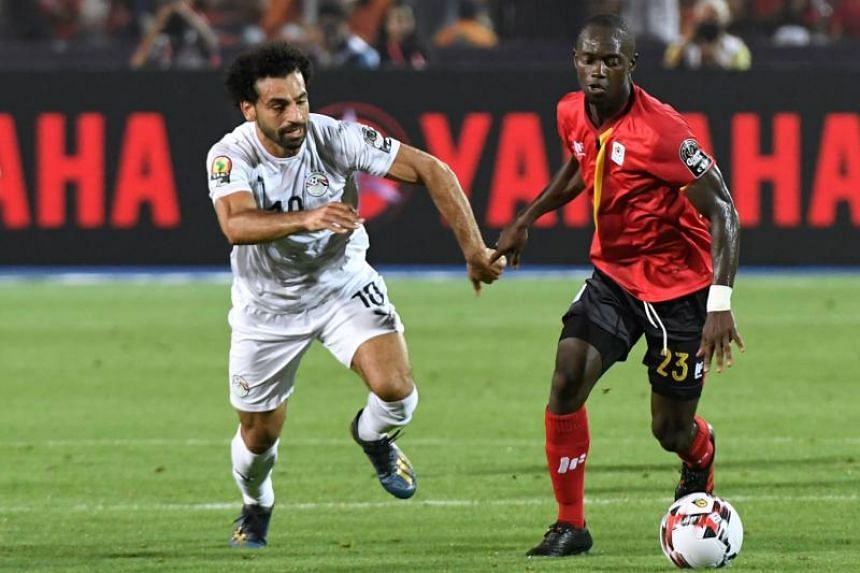 Egypt's forward Mohamed Salah (left) vies for the ball with Uganda's midfielder Michael Azira during the 2019 Africa Cup of Nations (CAN) Group A football match between Uganda and Egypt at the Cairo International Stadium in the Egyptian capital on Ju