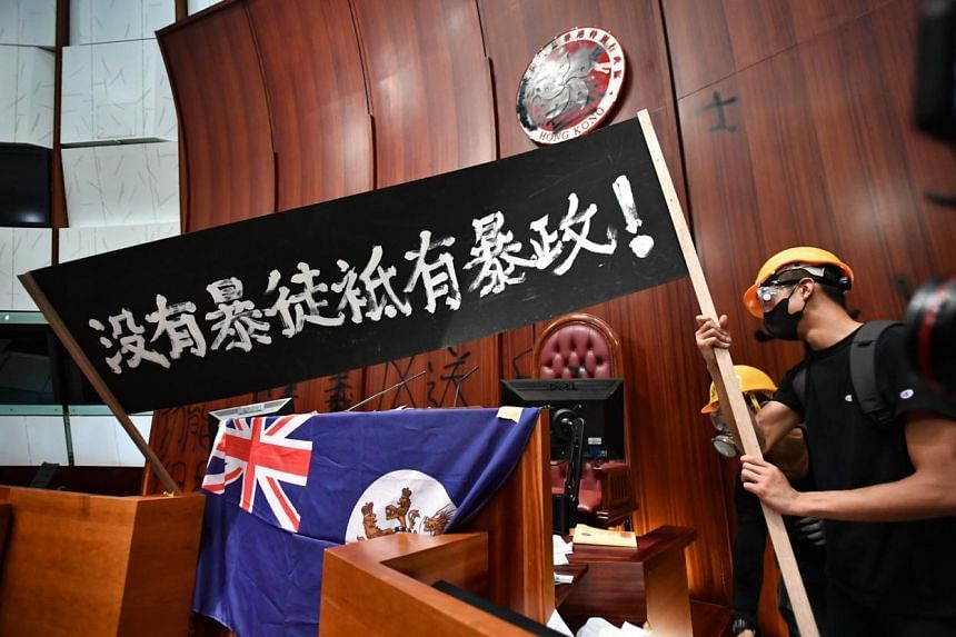Protesters wave a banner after breaking into the Legislative Chambers on July 1, 2019.