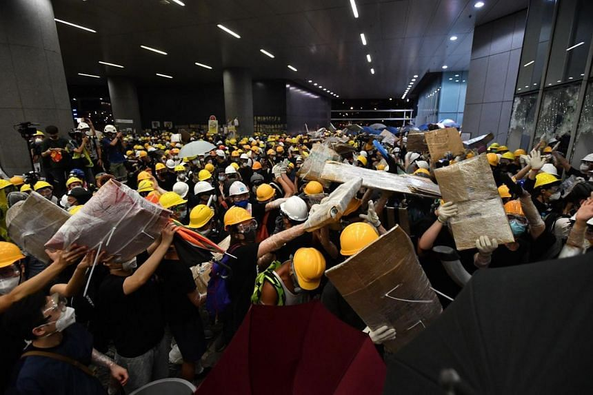 Protesters carrying supplies into the Legislative Council building after breaking through its doors on July 1, 2019.
