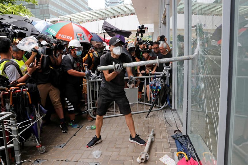 Protesters try to break into the Legislative Council building where riot police are seen, during the anniversary of Hong Kong's handover to China on July 1, 2019.