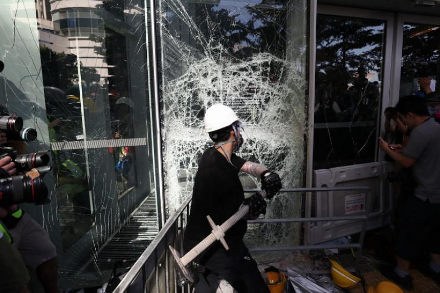A protester breaks a window of the Legislative Council in Hong Kong on July 1, 2019.