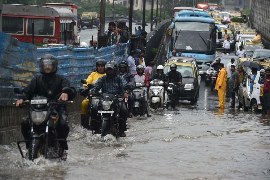 Indian motorists drive along a flooded street after heavy rain showers in Mumbai on July 1, 2019.