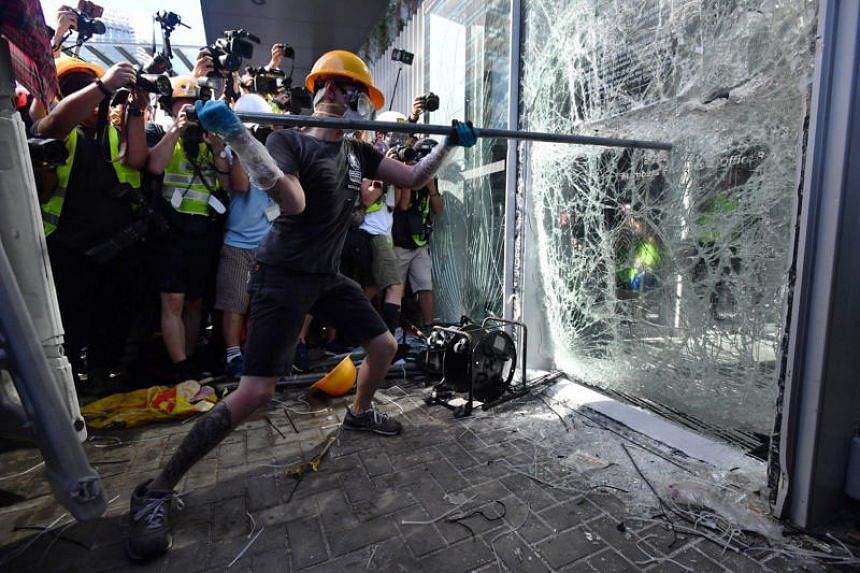 Protesters tried to storm Hong Kong's legislature using a metal trolley and poles to smash windows amid anger over planned legislation that would allow extraditions to China.