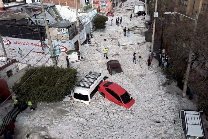 Vehicles buried in hail are seen in the streets in the eastern area of Guadalajara, Mexico, on June 30, 2019.