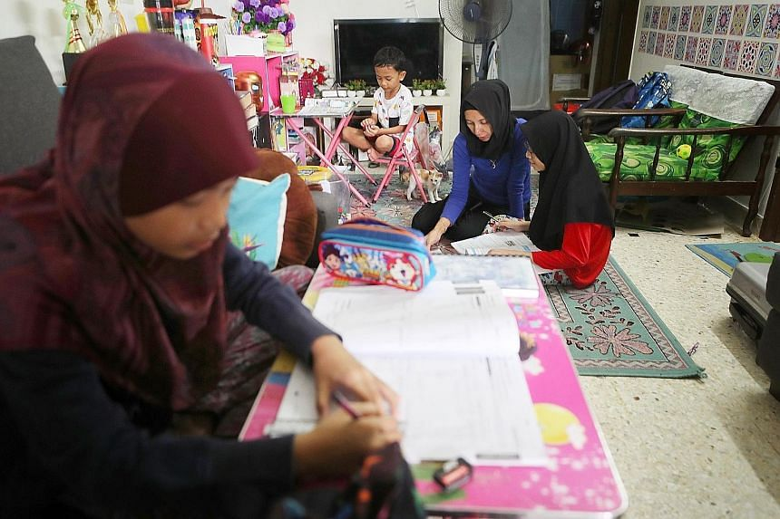 Pasir Gudang resident Azalila A. Samad and her children (from far left) Nur Kasih Farhana Mohd Kamil, 11, Muhammad Haidar, eight, and Nur Fatin Kamilia, 13. She has not allowed her two younger children to go to school until the situation improves.