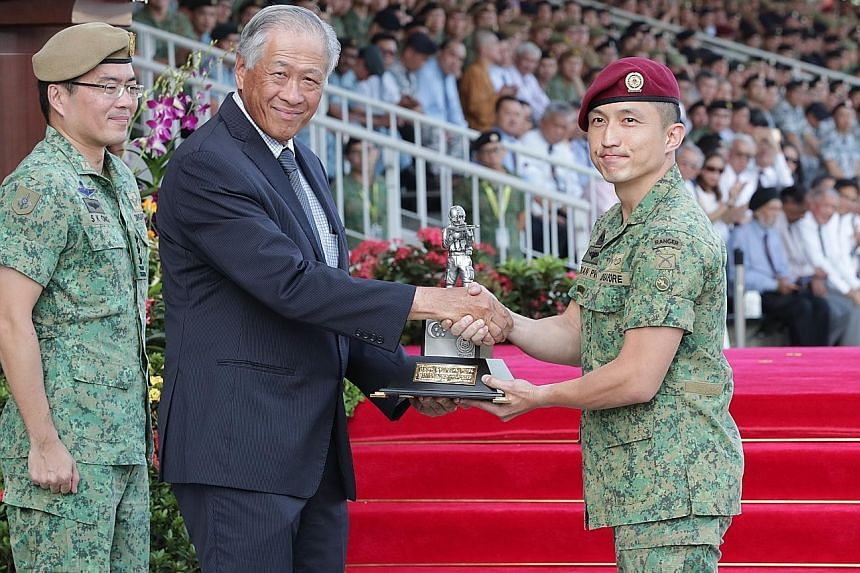 Lieutenant-Colonel Fabian Pwi (right), commanding officer of the 1st Commando Battalion, receiving the award for best unit from Defence Minister Ng Eng Hen during the Singapore Armed Forces Day Parade at the Safti Military Institute as the Chief of D