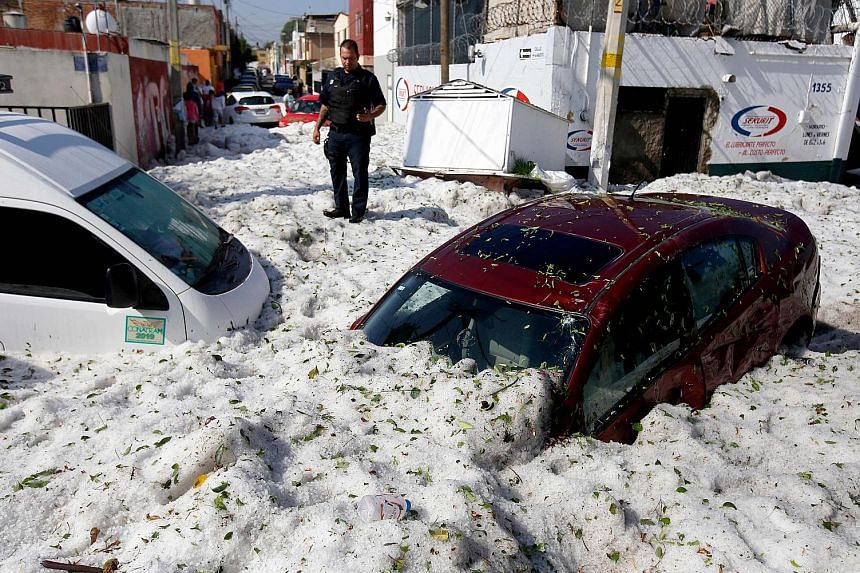The accumulation of hail in the streets of Guadalajara buried vehicles and damaged about 200 homes and businesses on Sunday.